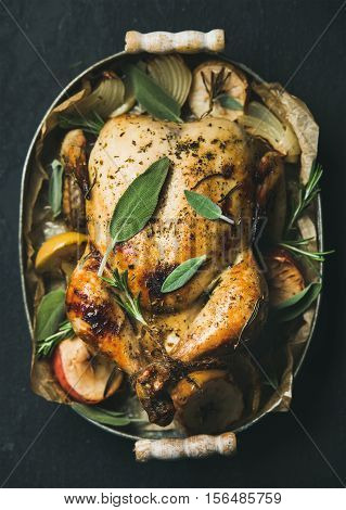Oven roasted whole chicken with onion, apples and sage in metal serving tray over dark stone background, top view, selective focus, vertical composition. Celebration food concept