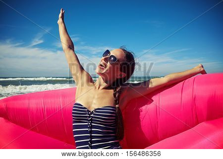 woman is sitting on the pink air rubber boat rejoicing and enjoying sunny and windy weather on the beach