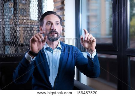 Virtual sensory screen. Nice handsome bearded man looking in front of him and touching the virtual sensory screen while sitting near the window