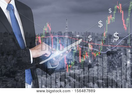 Businessman using digital tablet working with stock market chart in computer screen over the stock market exchange on tokyo cityscape in background Business trading and technology concept.