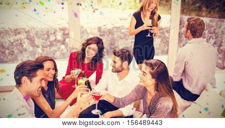 Group of friends toasting cocktail drinks against flying colours