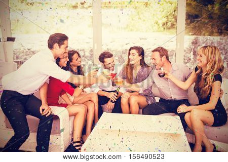 Group of friends toasting and having drinks against flying colours