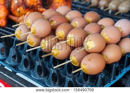 Yummy grill eggs on stove with smoke of charcoal eggs made from eggs and fish sauce stir together and put it in again. in local market Thailand.
