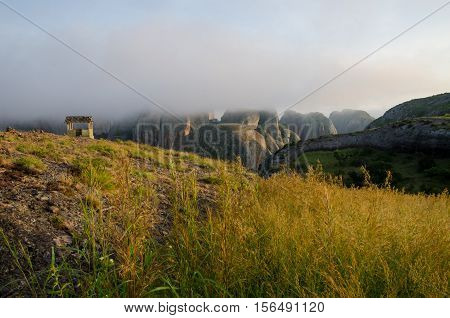 Fog and concrete hut at Black Rocks of Pungo Andongo or Pedras Negras in Angola. These unusual rock formations are of much darker color than their surrounding.