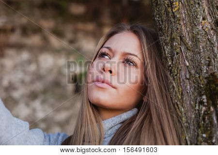 Beautiful woman next to the trunk of a tree on a day in autumn