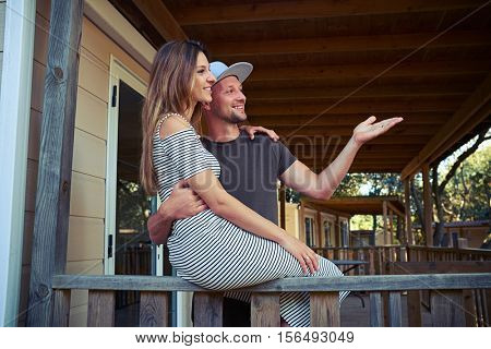 Close-up of a young couple who is happy to see their friends far off. An attractive young Caucasian brunette is sitting on the handrail and hugging her husband