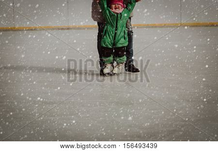 mother teaching child to skate in winter snow