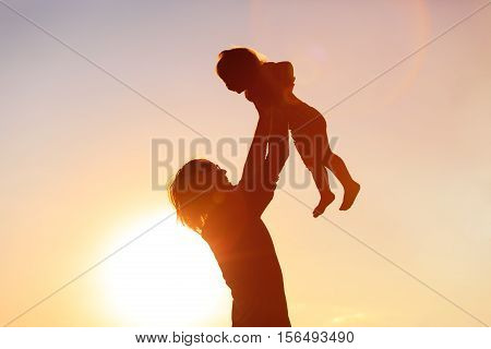 Father and little daughter silhouettes at sunset sky