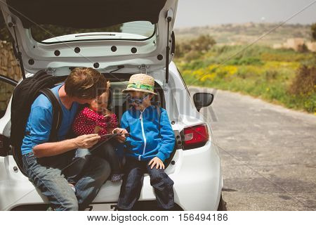 father with two kids looking at map while travel by car in nature