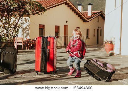 little girl with suitcases travel in Europe, family travel