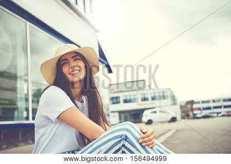 Woman With Whimsical Smile Seated On Curb
