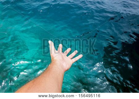 Hand of a young caucasian male appearing to touch the surface of amazing blue water of the Indian Ocean.