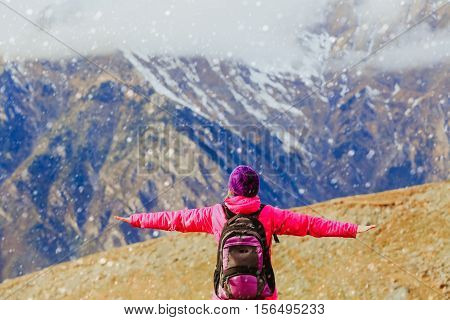travel concept- happy young woman hiking in snow scenic mountains