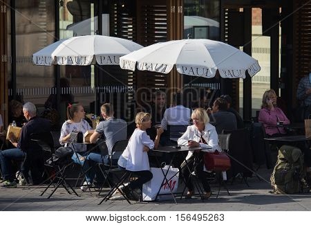 Nice France - November 3 2016: People enjoy a warm autumn day by sitting and meeting in an outdoor café in Nice France.