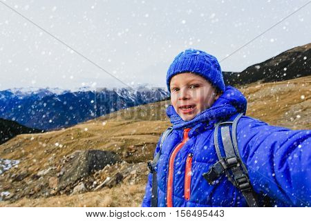 little boy making selfie while travel in mountains, family travel