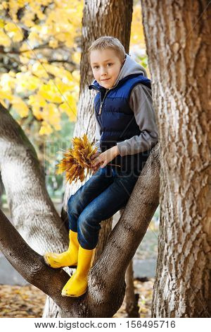 Portrait of happy cute little kid boy in blue vest and yellow rubber boots with autumn leaves.
