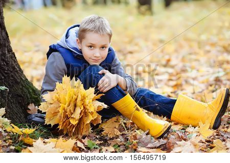 Portrait of happy cute little kid boy in blue vest and yellow rubber boots with autumn leaves background.