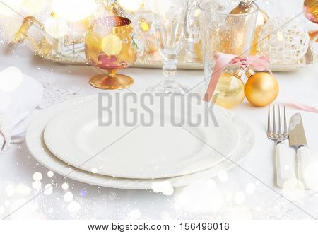 Tableware for christmas - set of empty plates and utencils on white tablecloth with defocused lights in background with bokeh lights