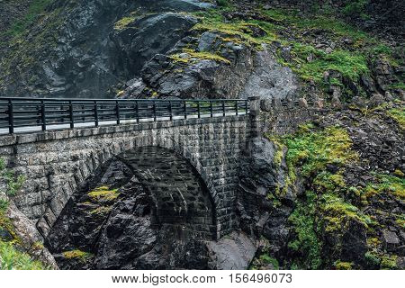 Stone bridge over a canyon at the Trolls path in Norway