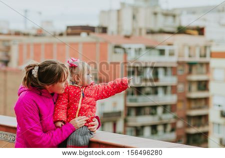 mother and little daughter looking at the city, family travel