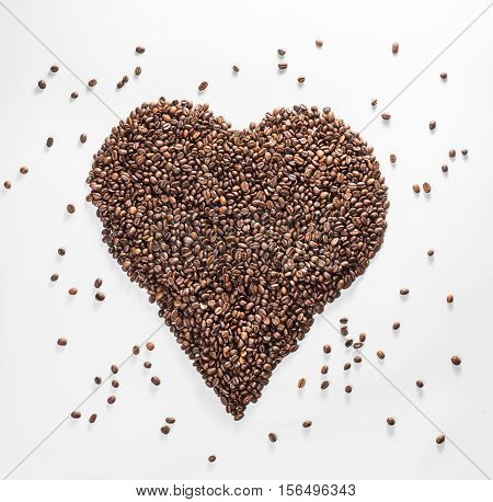 heart from coffee with scattered beans isolated on a white background.