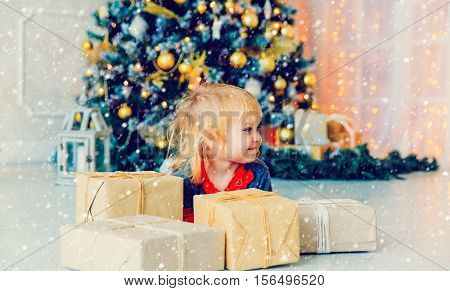 cute little girl opening christmas presents in decorated living room