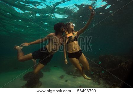 girl is taking a photo underwater of her and her boyfriend
