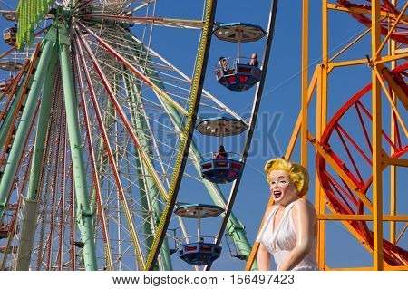 Closeup of a big observation wheel in the amusement park with the figure of Marilyn Monroe in the foreground. Bad Duerkheim, Germany - September 10 2016.