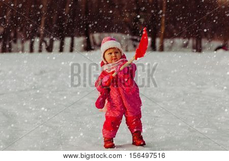 cute little toddler girl dig winter snow nature