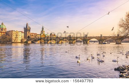 Prague city and Vltava river at sunset - Colorful landscape of the golden city Prague the capital of Czech Republic with the Charles Bridge and the Vltava river in the afternoon.