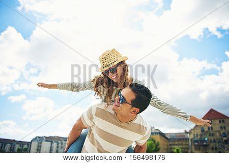 Young Couple Having Fun Piggy Backing
