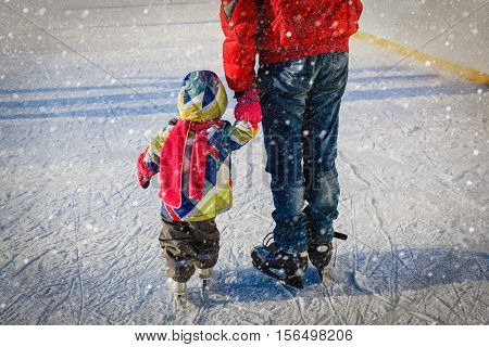 father teaching little daughter to skate in winter snow