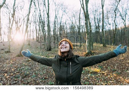 Young woman meditating with open arms standing in winter forest