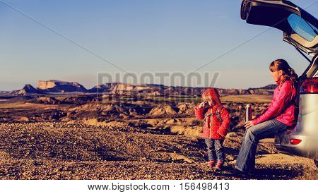 mother and little daughter travel by car in scenic mountains, panorama