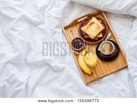 Breakfast in bed - french toasts with a cup of coffee.