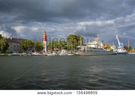 Lighthouse in the seaside town and ships at berth.