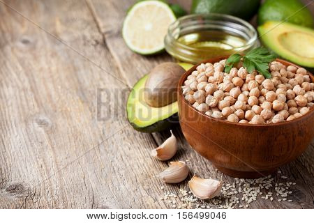 Ingredients for cooking with avocado hummus: chickpeas avocados olive oil sesame garlic lime on the old wooden background
