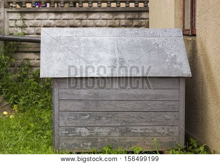 Old wooden dog house for dog with tin roof  in yard