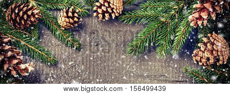 Christmas nature decorations with fir branches and pine cones over old wood background. Christmas banner with copy space