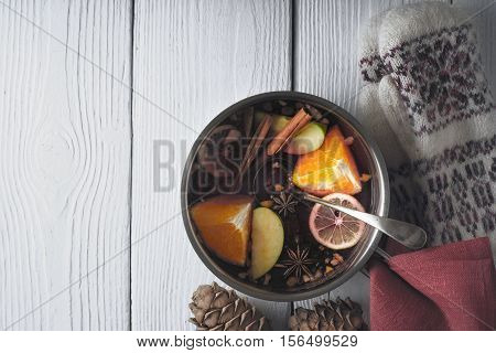 Pot with mulled whine on the white wooden table horizontal