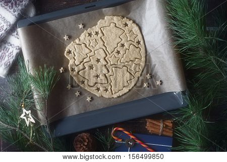Christmas cookie preparation on the wooden table with different accessorizes
