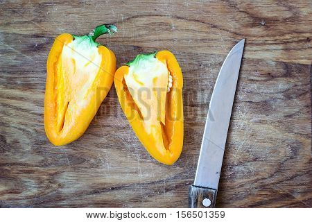 Chopped cut colorful vibrant bright yellow fresh ripe sweet pepper and kitchen knife on old cutting wooden board table background isolated top view close up bell pepper food