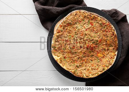 Lahmacun turkish homemade pizza with minced beef or lamb meat, paprika, tomatoes, cumin spice, parsley baked spicy middle eastern arabian food on white wooden table background