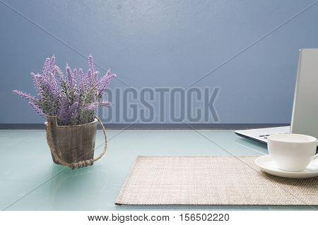 Glasses office table with white cup of coffee laptop and purple lavender flower on pot Concept of office life and mock up free space for advertisement.