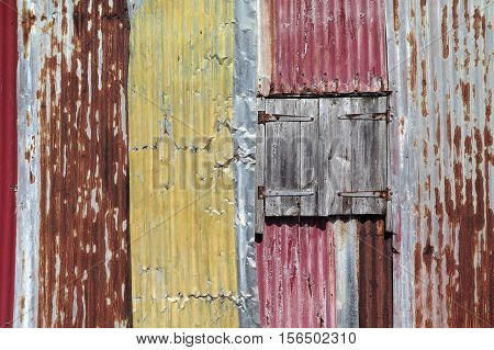 Detail of a Creole hut made of corrugated sheets and a window with wooden shutters. Patined by time and elements. Natural colors and light. / Background of wavy and patined metal / Basse Terre, Guadeloupe, French West Indies.