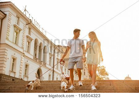 Happy couple going down stairs with dogs on leash outside i a city