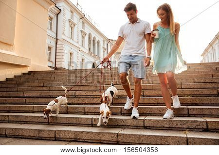 Young couple walking down stairs with their dogs on a city street