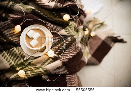 Cozy winter home, cup of coffee with marshmallows, warm blanket and Christmas lights