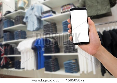 human hand hold smartphone tablet cell phone with blurry Clothing racks. concept of shopping and finding clothes on application online.