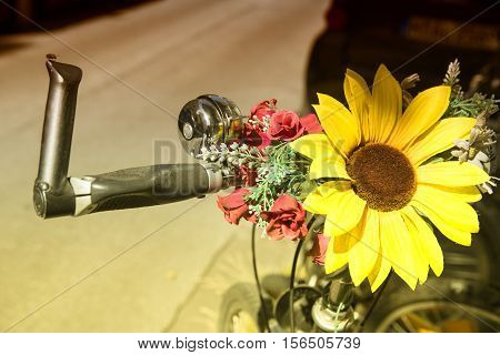 closeup of bicycle handlebar with sunflower and bell